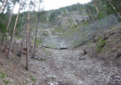 The construction site is threatened by two main gullies. Multiple lines of protection netting are designed to keep rocks from reaching the valley bottom.