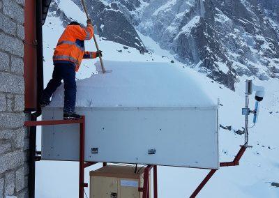 Winter 17/18: Das Georadar zur Überwachung des Pizzo Cengalos muss viel aushalten: Ein Mitarbeiter schaufelt bei Wartungsarbeiten Schnee vom Dach.